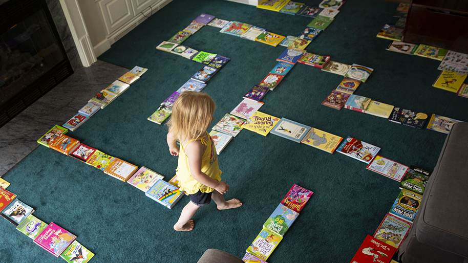 Little girl walking through a book maze