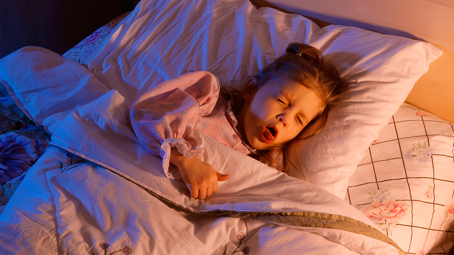 Little girl lying in bed and coughing