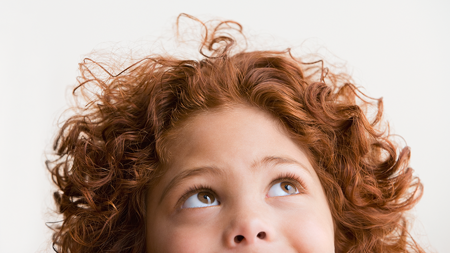 Child with curly red hair looking up