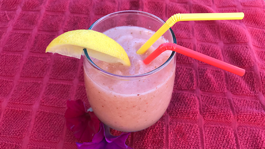 Glass of strawberry lemonade slushee with a straw