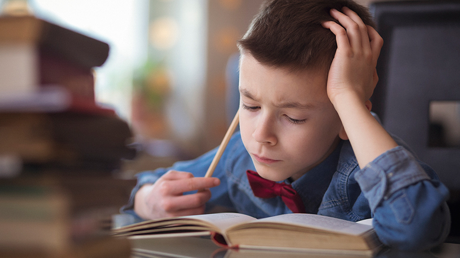 Boy looking troubled as he reads a book
