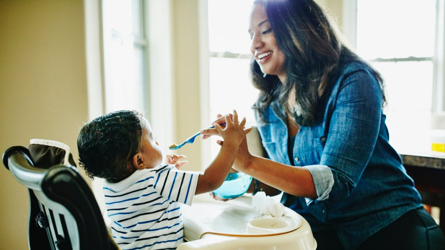 Mother feeding a baby. in a highchair