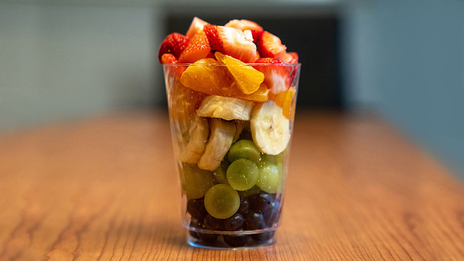 Cup with layered blueberries, grapes, bananas, oranges, & strawberries