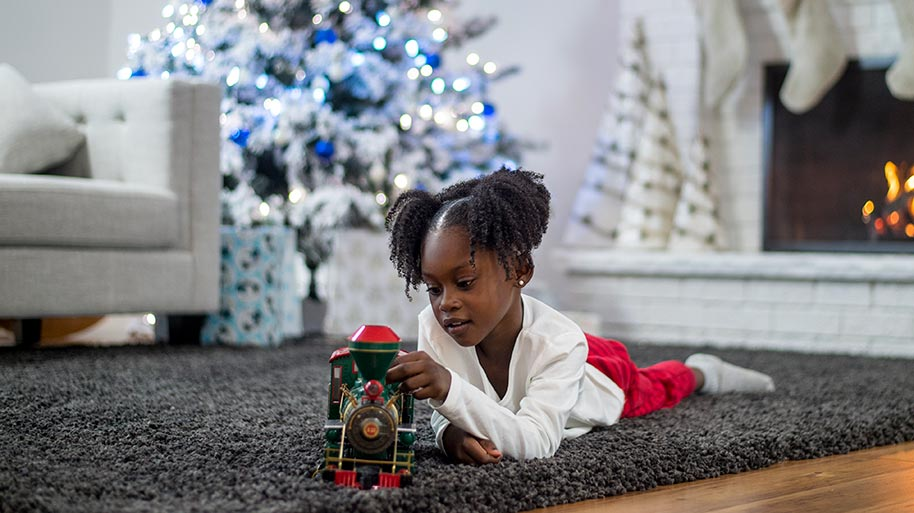 Little girls playing with a train in front of a Christmas tree