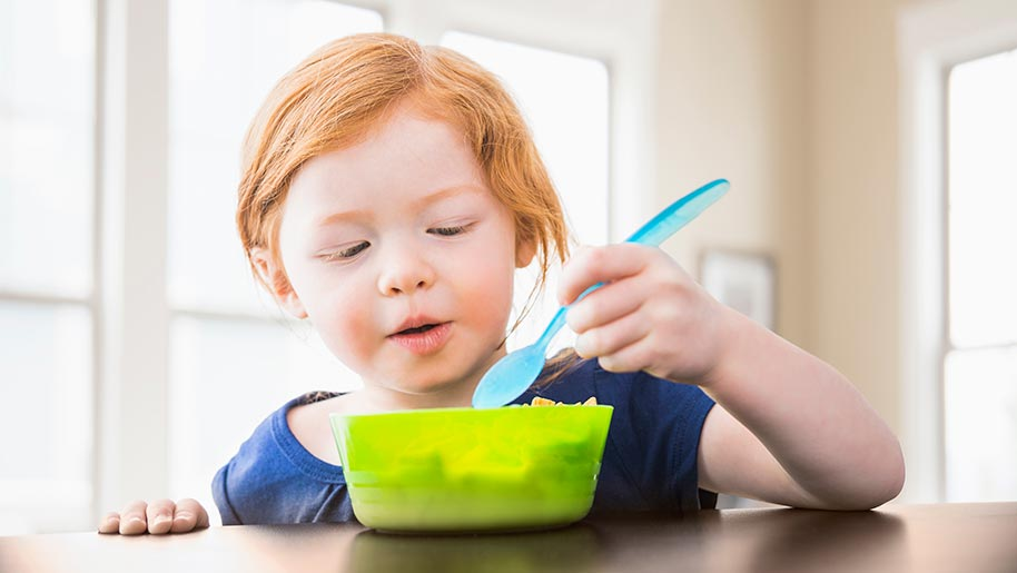 Child eating from a green bowl
