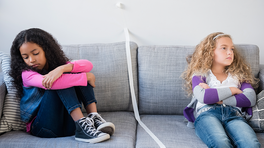 Two girls on a sofa arguing