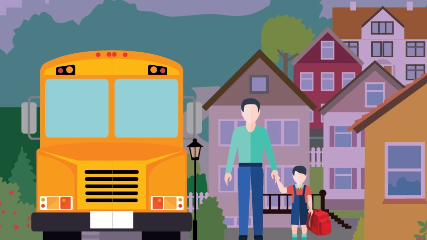 Photo of parent and child standing next to school bus