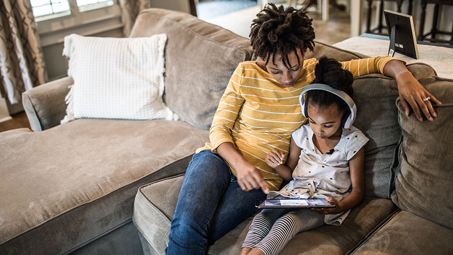 Mother and young girl holding an ipad sitting on a brown sofa.