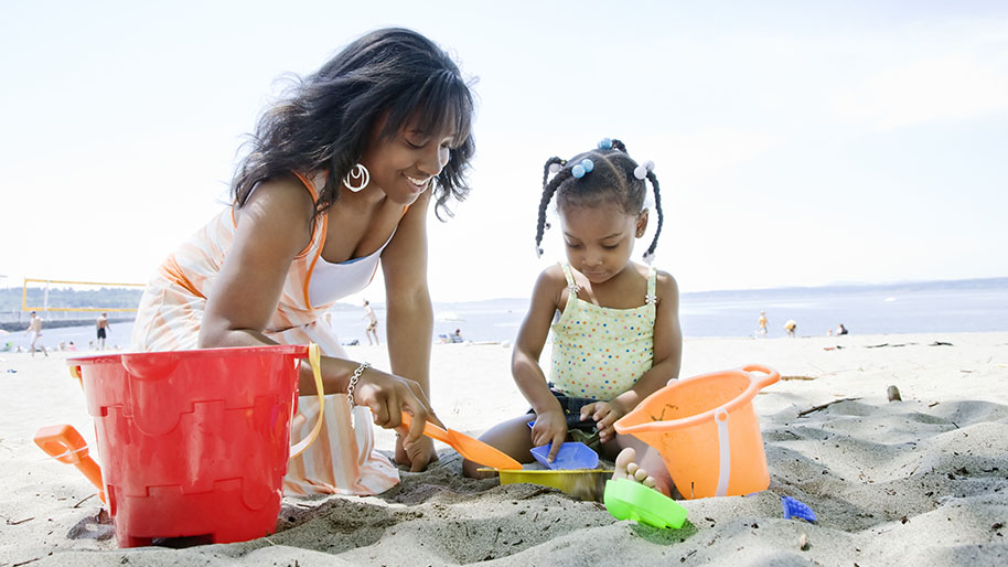Mother and young girl playing in the sand with orange and yellow buckets; Ocean in the background