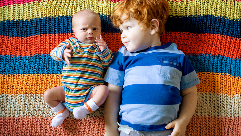 Toddler boy laying next to a baby