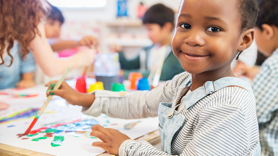 Child painting in a classroom setting