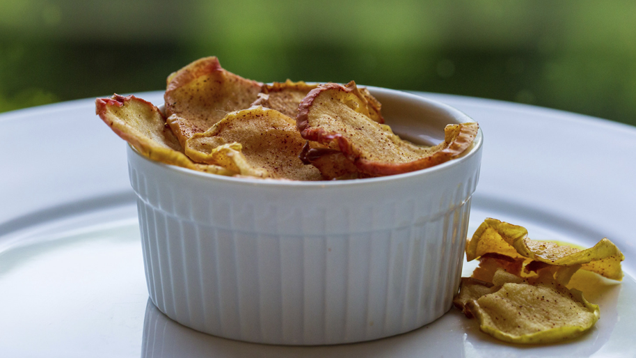 White bowl filled with cinnamon apple chips