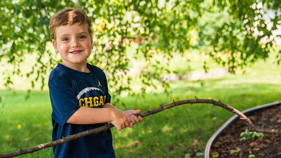 Five year old Carter standing under a tree and holding a big stick