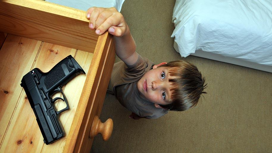 Little boy reaching into a drawer for a gun
