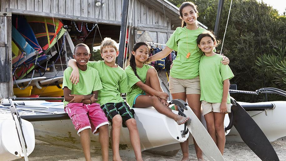 Two boys and two girls with there camp counselor sitting on a sailboat in the sand; boat house in the background