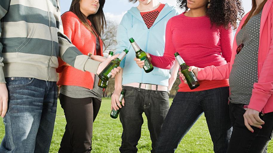 Five teens with beer bottles in their hands