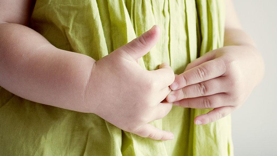 Child's hands rubbing her stomach over a green top