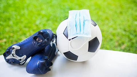 Soccer ball and cleats and a facemask