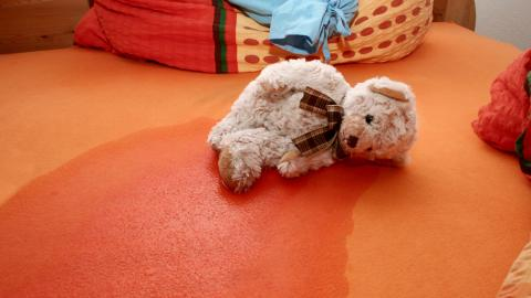 Teddy bear laying on a wet sheet