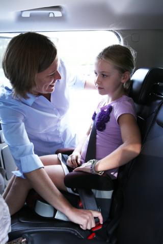 Dr. Michelle Macy buckles a child into a safety seat.