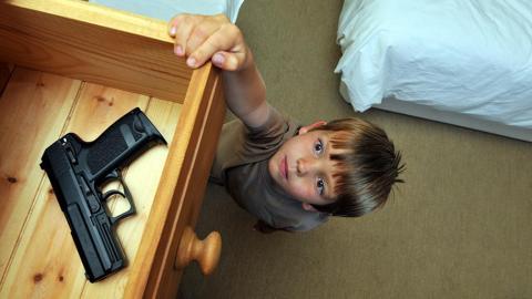 Little boy reaching into a drawer for a gun