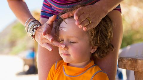 Woman rubbing sunscreen on a childs nose