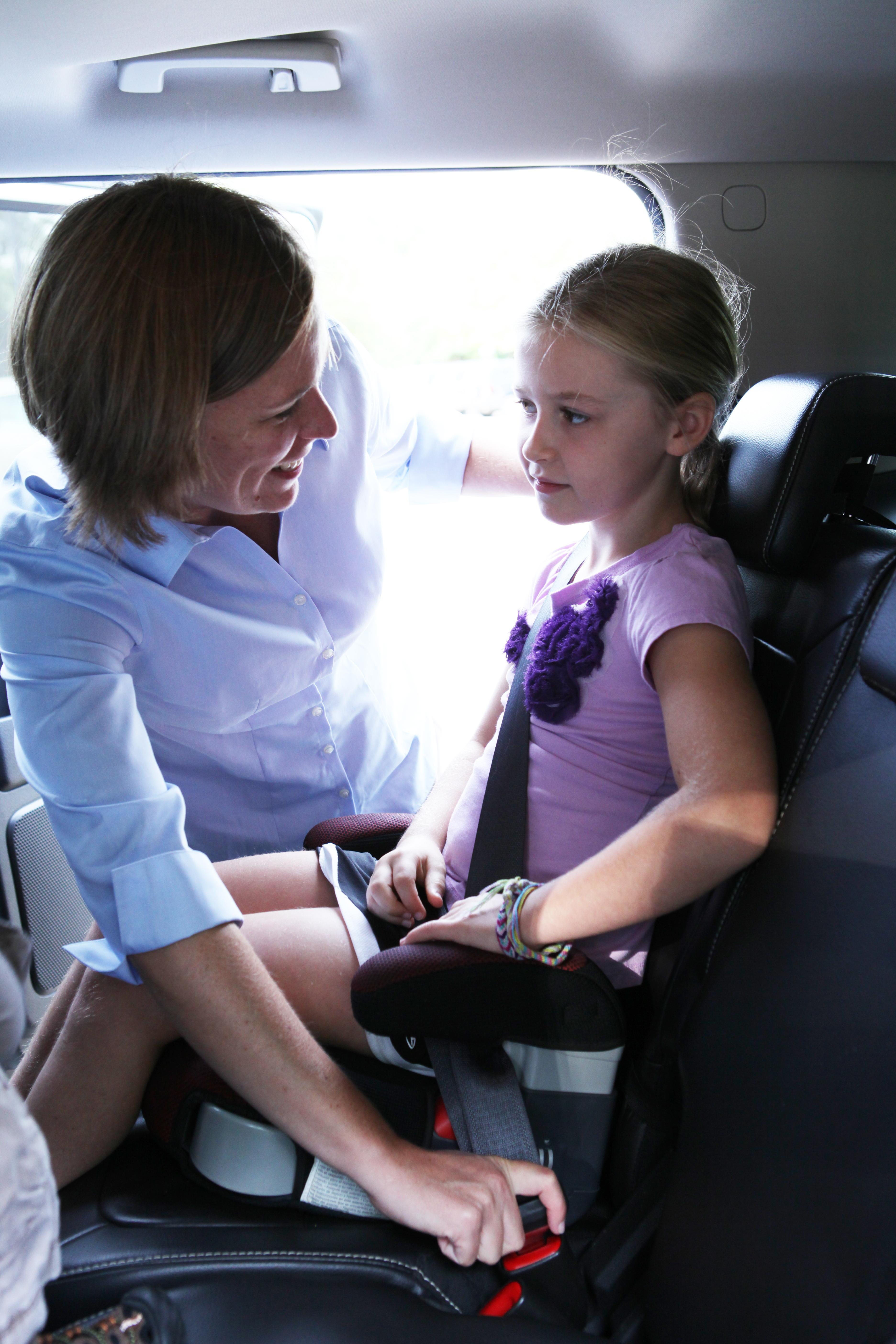 Michelle Macy, M.D., buckles child into car seat.