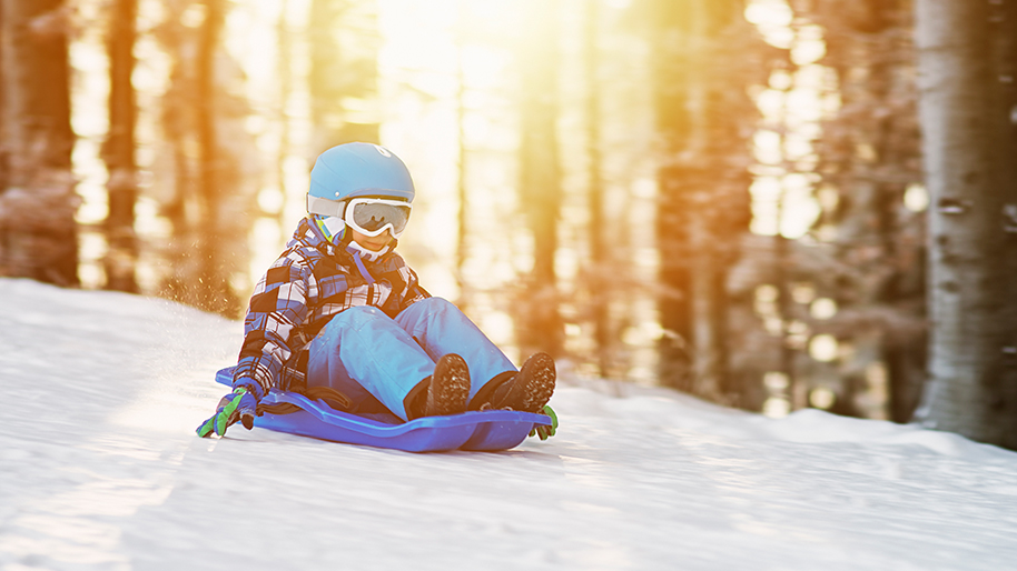 Child sledding down a hill with trees in background